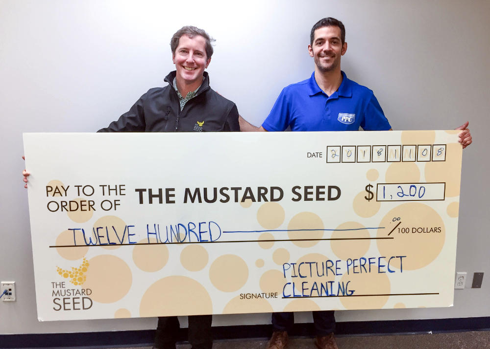 Jared Sarbit and CFO Walter Kurz standing beside each other holding a donation cheque for $1,200 CAD for the Mustard Seed