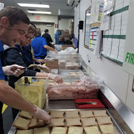 A Picture Perfect Cleaning team member preparing sandwiches for the homeless
