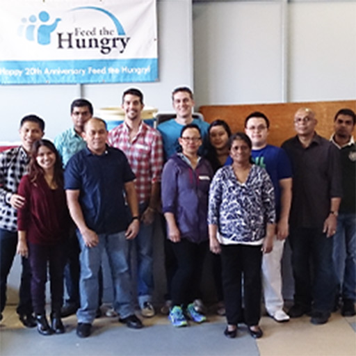 Jared Sarbit and Aaron Graham stand with a group of people at the Feed the Hungry building